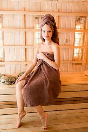 Young woman relaxing in a sauna dressed in a towel. Interior of new Finnish sauna, infrared panels for medical procedures, classic wooden sauna.