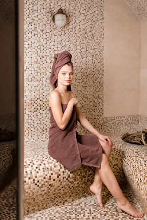 Attractive woman relaxing in a hammam - turkish steam bath with ceramic tile in roman style Banque d'images