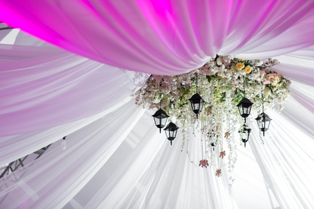Chandelier made of roses and white flowers hangs under the light tent. decorative lights