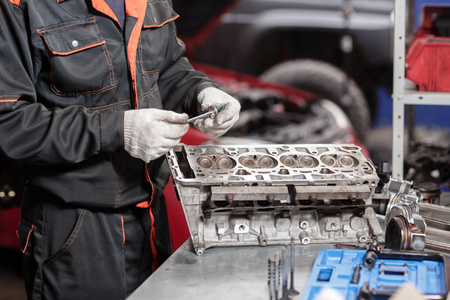 Selective focus. Engine Block on a repair stand with Piston and Connecting Rod of Automotive technology. Blurred red car on background. Interior of a car repair shop Stok Fotoğraf