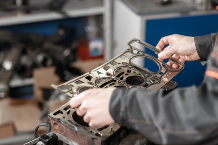 El mecánico desmonta el vehículo del motor de bloque. Motor en un soporte de reparación con pistón y biela de tecnología automotriz. Interior de un taller de reparación de automóviles Foto de archivo