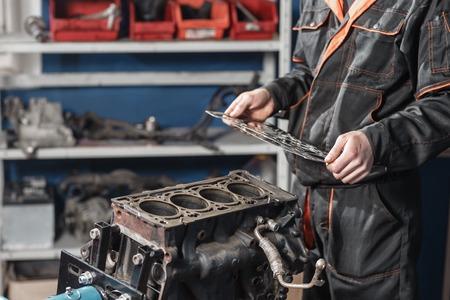 Der Mechaniker zerlegt Blockmotorfahrzeug. Motor auf einem Reparaturständer mit Kolben und Pleuel der Kraftfahrzeugtechnik. Innenraum einer Autowerkstatt
