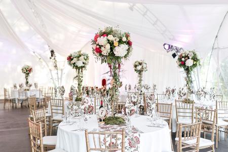 Interior de una tienda de boda decoración lista para invitados. Mesa redonda para banquetes servida al aire libre en marquesina decorada con flores y seda. Concepto de catering.
