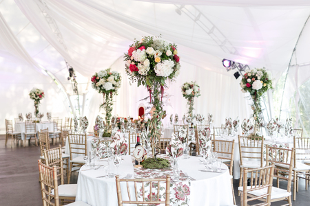 Interior of a wedding tent decoration ready for guests. Served round banquet table outdoor in marquee decorated flowers and silk. Catering concept.