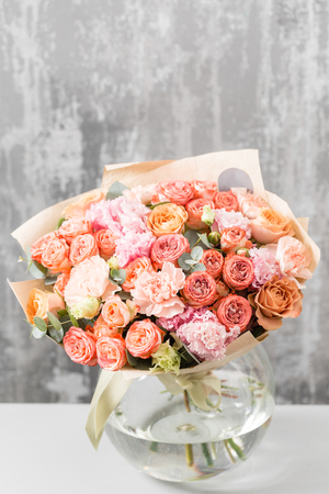 beautiful bouquet of mixed flowers in a vase on wooden table. the work of the florist at a flower shop. Stock Photo