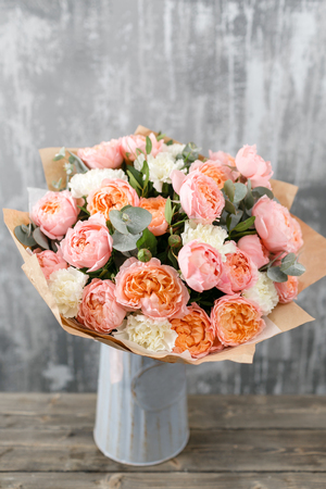 beautiful luxury bouquet of mixed flowers in glass vase . the work of the florist at a flower shop. wooden table and old wall Stockfoto