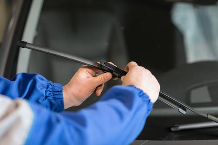 Il tecnico sta cambiando i tergicristalli del parabrezza su una stazione di automobile. Archivio Fotografico - 93319087