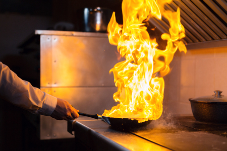 Flambe lamb rib roast. Cooking with fire in frying pan. Professional chef in a commercial kitchen cooking. Man frying food in flaming pan on hob in outdoor kitchen. slow motion Stockfoto
