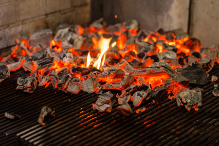 Typical Argentinian barbecue or asado. Burning wood in the grill and red hot coals