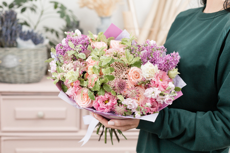 beautiful luxury bouquet of mixed flowers in woman hand. the work of the florist at a flower shop. cute lovely girl Banque d'images