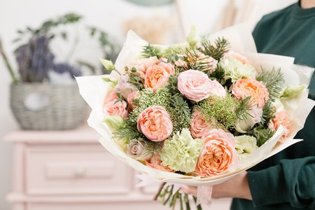beautiful luxury bouquet of mixed flowers in woman hand. the work of the florist at a flower shop. cute lovely girl Banco de Imagens