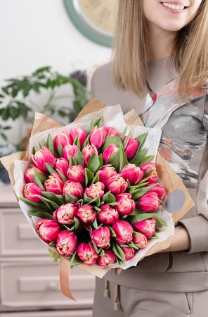 Beautiful luxury bouquet of pink tulips flowers in woman hand. the work of the florist at a flower shop. cute lovely girl
