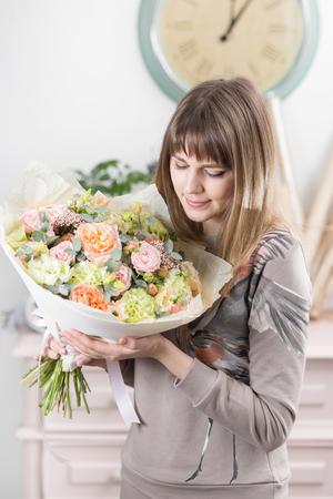Mooi luxeboeket van gemengde bloemen in vrouwenhand. het werk van de bloemist in een bloemenwinkel. schattig lief meisje