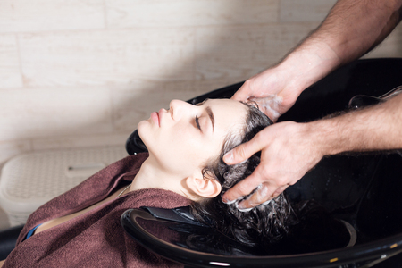 beautiful girl washes her hair before a haircut in a beauty salon. hair washing at a hairdressing, young caucasian girl. professional shampoo. stylist hairdresser man