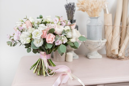 beautiful luxury bouquet of mixed flowers on pink table. the work of the florist at a flower shop. Wedding 免版税图像 - 94260397