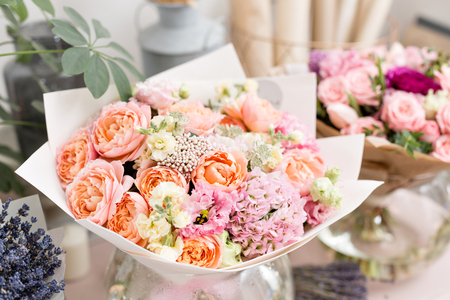 Few of beautiful luxury bouquet. Mixed flowers on pink table. the work of the florist at a flower shop. Wedding