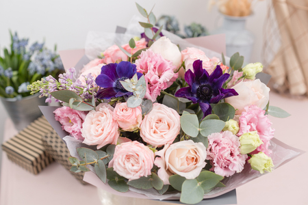 beautiful luxury bouquet of mixed flowers on pink table. the work of the florist at a flower shop.