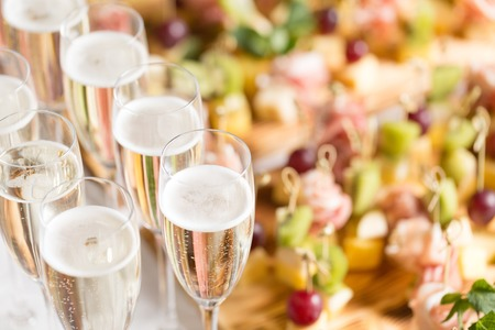 Furshet. Table top full of glasses of sparkling white wine with canapes and antipasti in the background. champagne bubbles Stock Photo