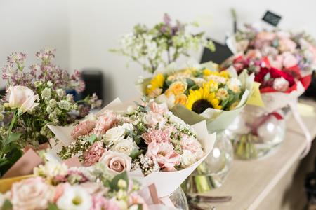 Bouquets on table, florist business. Different varieties fresh spring flowers. Delivery service. Flower shop concept. Archivio Fotografico