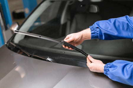Technician is changing windscreen wipers on a car station.