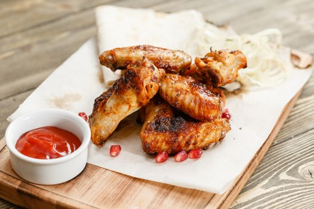 chicken wings grill. Serving on a wooden Board on a rustic table. Barbecue restaurant menu, a series of photos of different meats