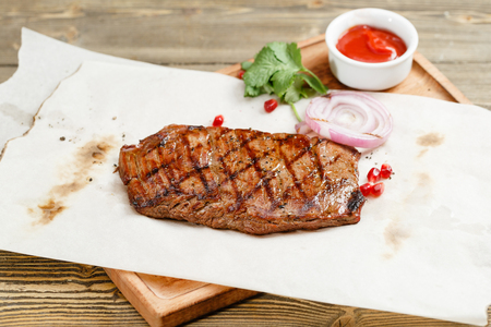 steak of marble beef, grilled. Serving on a wooden Board on a rustic table. Barbecue restaurant menu, a series of photos of different meats