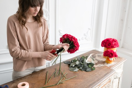 Young woman florist arranging plants in flower shop. People, business, sale and floristry concept. Bouquet of red roses Stock Photo