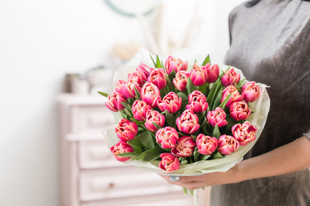 beautiful luxury bouquet of pink tulips flowers in woman hand. the work of the florist at a flower shop.