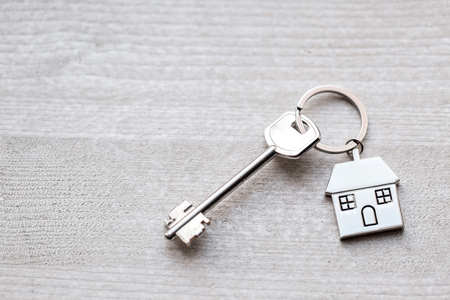 House key and keychain in the form of homes lies on wooden boards. Concept for real estate, mortgage, moving home or renting property.