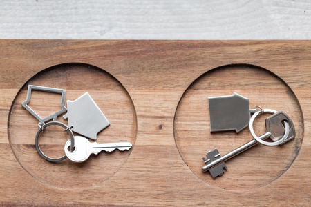 Two House key and keychain in the form of homes lies on wooden boards. Concept for real estate, mortgage, moving home or renting property. Stock Photo