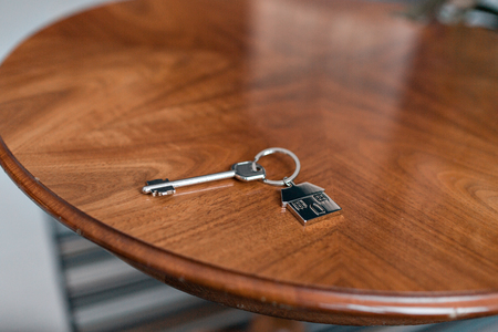 House key and keychain in the form of homes lies on wooden table. Concept for real estate, mortgage, moving home or renting property. Stok Fotoğraf