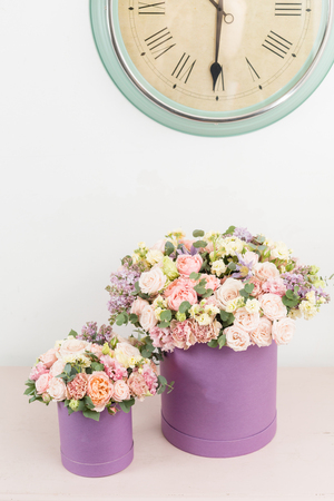 beautiful luxury bunch of mixed flowers on pink table. the work of the florist at a flower shop. bouquet in lilac hatbox. perfect gift or compliment.