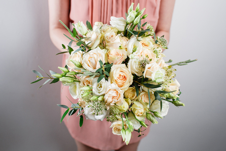 beautiful luxury bouquet of mixed flowers in woman hand. the work of the florist at a flower shop
