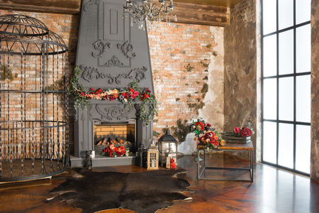 Interior with fireplace, candles, skin of cows, brick wall, large window and a metal cell of a loft, living room, coffee table in modern design