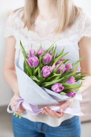 close up. Young happy woman holding a beautiful bunch of violet tulips in her hands. Present for a smiles girl. Flowers bouquet. Sunny spring morning. Foto de archivo