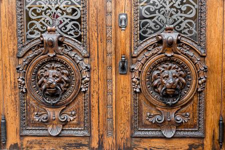 Old Wooden Door. Big Two Heads Of Lion On The Front . Vintage Door Knocker