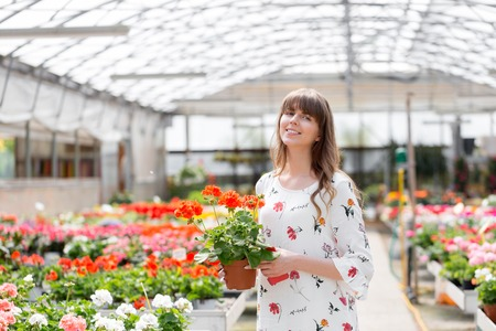 Young woman buying flowers at a garden center. Woman looking at flowers in a shop. Portrait of a smiling woman with flowers in plant nursery. My favorite flowers.