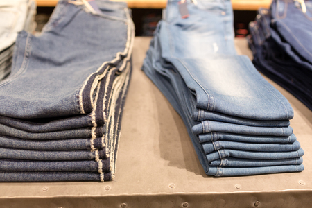 stack of blue jeans in a shop. shopping sale background theme. clothes on hanger in shop
