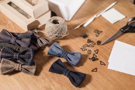 lots of ready made butterfly bow ties made of wool in the foreground, adds a finished product. Good looking young man working as a tailor and using a sewing machine in a textile studio.
