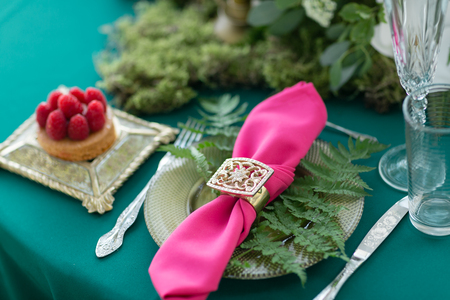 Pink napkin with a patterned clip. table setting. Wedding decor in the magic forest for a loving couple. Pink and green colors.