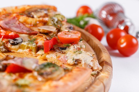 Italian kitchen and cooking concept. Hot tasty sliced with ham, sausage, jalapenos, mushrooms, tomato. Eat delivery concept.