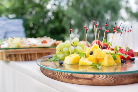 Wooden plate with sliced fruits and berries on a buffet table. Summer party outdoor. Horizontal photo