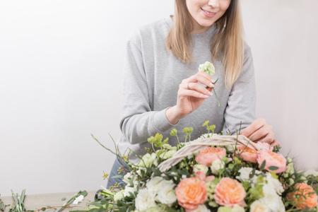 Smiling female florist. Floral workshop - woman making a beautiful flower composition a bouquet in a wicker basket. Floristry concept