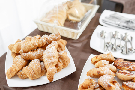 Fresh croissants on white plate. French traditional pastry. Breakfast in hotel smorgasbord.
