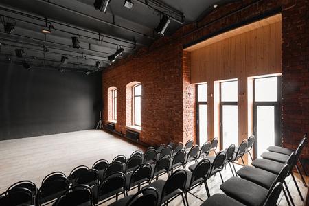 Loft style. Hall with black chairs for webinars and conferences. A huge room with large Windows, surrounded by brickwork, and parquet floors. For film and theatre productions
