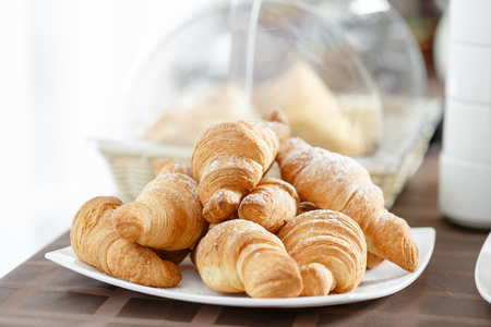Fresh croissants on white plate. French traditional pastry. Breakfast in hotel smorgasbord. Stock Photo - 99295291