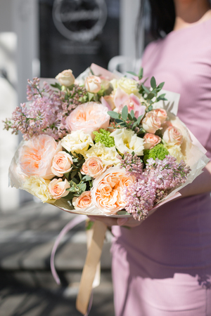 bouquet of beautiful flowers in womens hands. Floristry concept. Spring colors. the work of the florist at a flower shop. Vertical photo