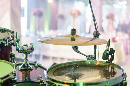 Drum kit on stage. Close-up of plate, drums, sticks, in background scene spotlights