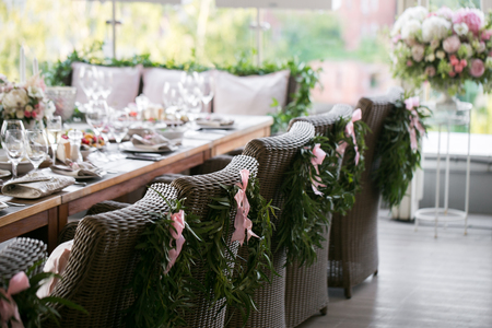 Garland of flowers and greenery for table decoration. Luxury wedding reception in restaurant. Stylish decor and adorning. Tables served with beautiful dishes and delicious food