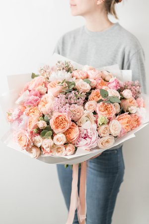 bouquet of beautiful flowers in womens hands. Floristry concept. Spring colors. the work of the florist at a flower shop. Stock Photo